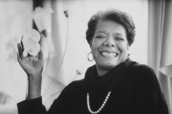 8th January 1993: Headshot portrait of African-American author Maya Angelou wearing black sweater with a pearl necklace, smiling and holding flowers in one hand. (Photo by Stephen Matteson Jr/New York Times Co./Getty Images)